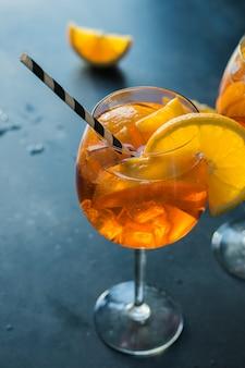 Klassisches italienisches aperol spritz cocktail auf dunkelheit.