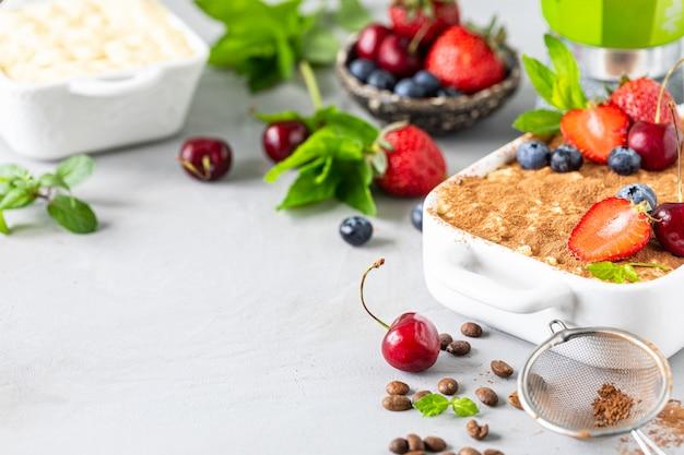 Klassisches italienisches dessert tiramisu verziert mit erdbeeren, kirschen und minze auf einem weißen hintergrund. kopieren sie platz für ihren text.
