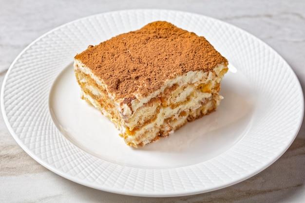 Klassisches italienisches dessert tiramisu von ladyfingers oder savoiardi in espresso und mascarpone getränkt mit geschlagenem eiweiß, serviert auf einem weißen teller mit frischer minze auf einem marmortisch, nahaufnahme