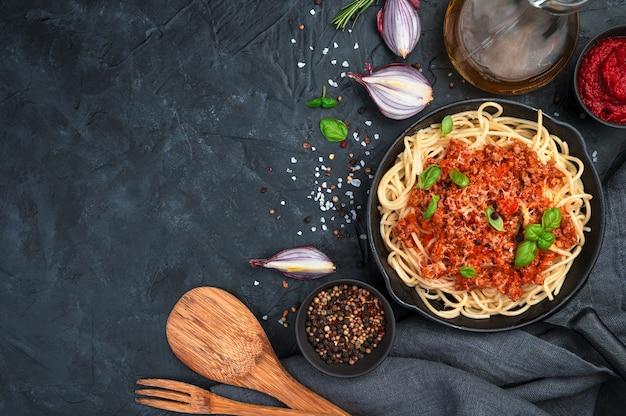 Klassisches italienisches gericht pasta bolognese mit basilikum auf dunklem hintergrund. kochkonzept.