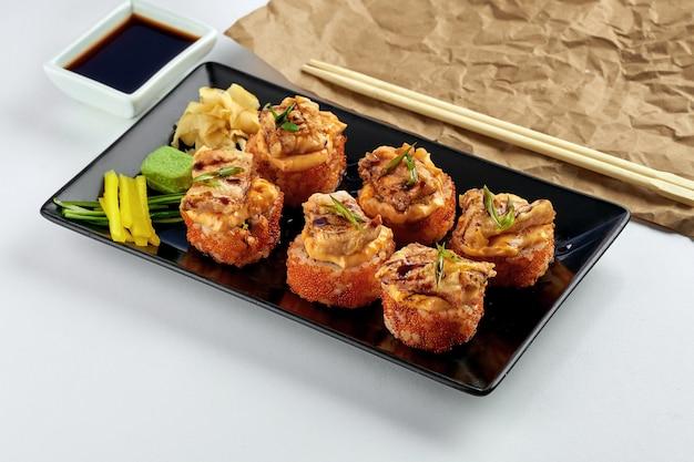 Klassisches japanisches essen - kalifornisches sushi-brötchen mit gebackenem lachs und würziger sauce, tobiko-kaviar, serviert in einem schwarzen teller auf einem weißen teller