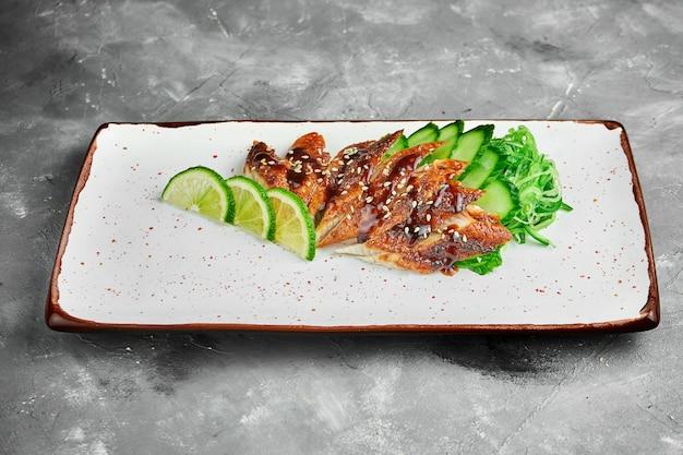 Klassisches japanisches sashimi-set von rohem aal mit limette, gurke auf einem weißen teller auf einem grauen tisch. nahaufnahme, selektiver fokus