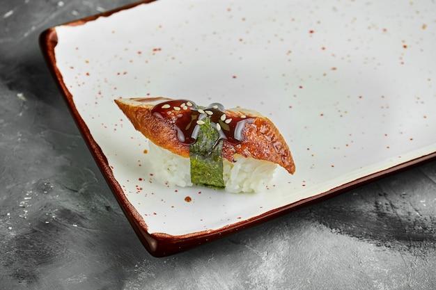 Klassisches japanisches sushi mit aal, unagi, sesam und nori auf einem weißen teller auf einem grauen tisch. japanische küche. nahaufnahme, selektiver fokus
