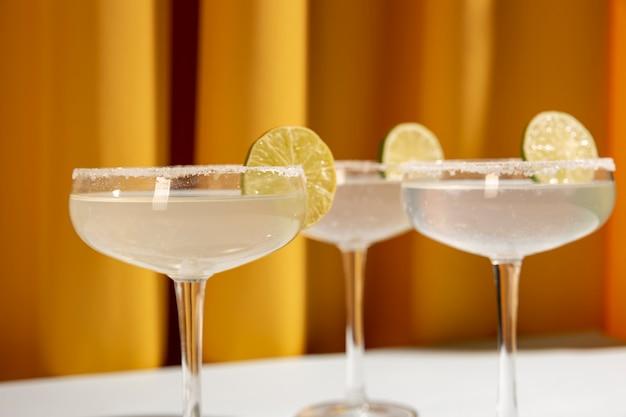 Klassisches limetten-margarita-cocktail mit geschnittenen limetten gegen gelben vorhang