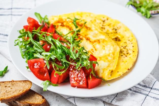 Klassisches omelett mit käse-tomaten-salat auf einem weißen teller.