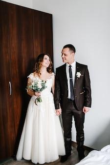 Klassisches porträt der braut und des bräutigams des raumes. glücklicher tag junges paar. das konzept des urlaubs und der liebe in der familie. hochzeitstag.
