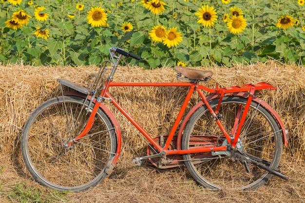 Klassisches rotes fahrrad mit sonnenblumenhintergrund