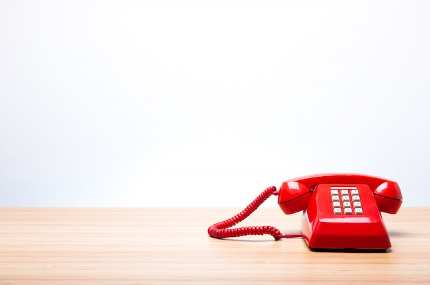 Klassisches rotes telefon auf hölzernem schreibtisch