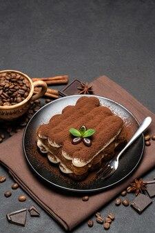 Klassisches tiramisu-dessert auf einer keramikplatte auf dunklem betonhintergrund