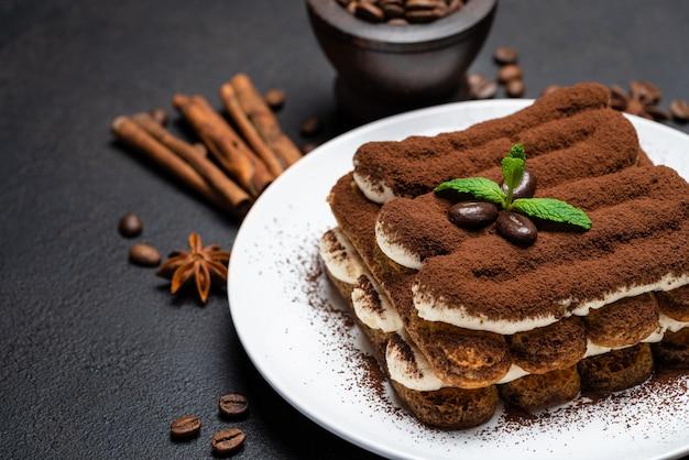 Klassisches tiramisu-dessert auf keramikplatte auf betonhintergrund