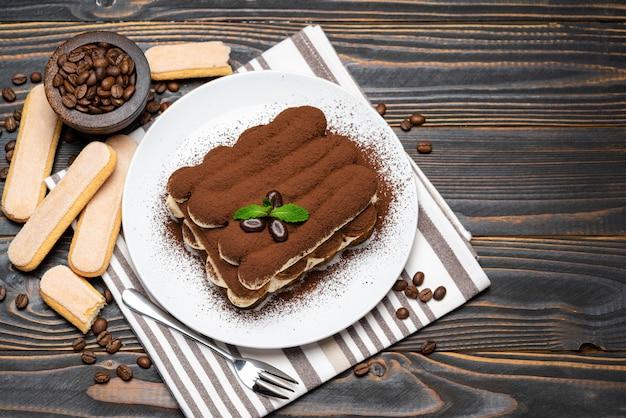 Klassisches tiramisu-dessert auf keramikplatte auf holzwand oder tisch