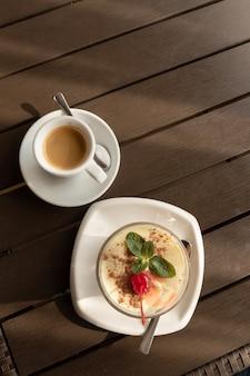Klassisches tiramisu-dessert in glas und tasse kaffee. menü cafe.