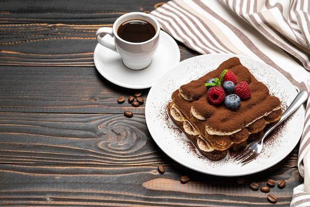 Klassisches tiramisu-dessert mit beeren und einer tasse espresso