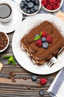 Klassisches tiramisu-dessert mit himbeeren, blaubeeren und einer tasse espresso