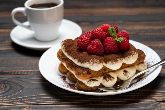 Klassisches tiramisu-dessert mit himbeeren und einer tasse espresso