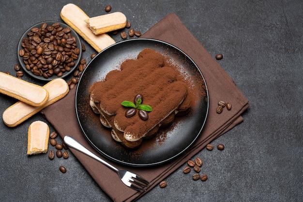 Klassisches tiramisu-dessert und savoiardi-kekse auf keramikplatte auf betontisch