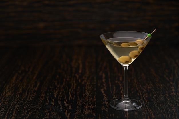 Klassisches trockenes alkoholisches getränk mit grünen oliven auf schwarzem holztisch.