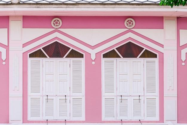 Klassisches weiß- und holzfenster an einem rosa konkreten gebäude.