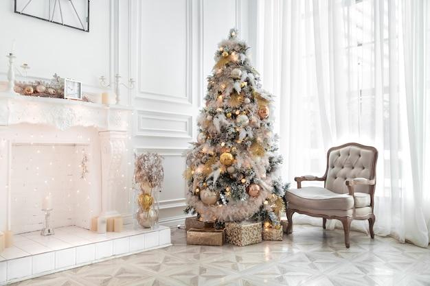 Klassisches weißes weihnachtsinterieur mit geschmücktem weihnachtsbaum. kamin mit grauem stuhl, uhren an der wand und geschenken unter dem baum