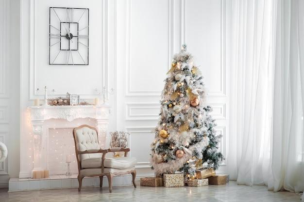 Klassisches weißes weihnachtsinterieur mit verziertem baum. kamin mit grauem stuhl, uhren an der wand und geschenken unter dem baum