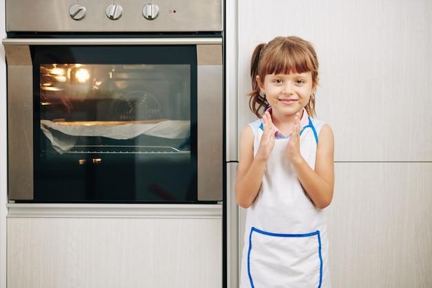 Klatschendes lächelndes mädchen, das am ofen in der küche steht und darauf wartet, dass kuchen gebacken wird
