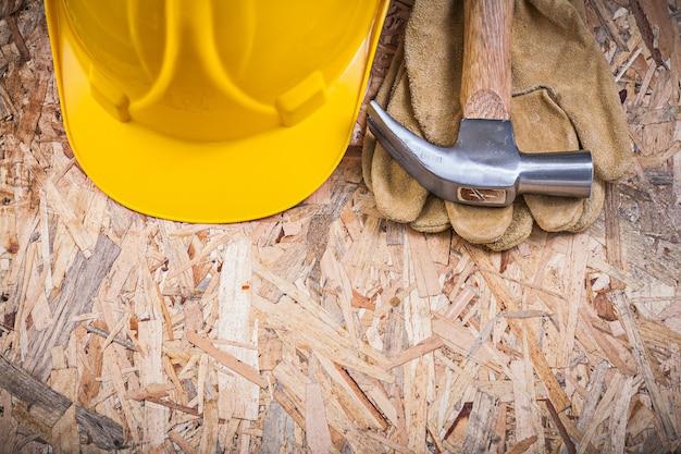 Klauenhammerbauhelm-sicherheitshandschuhe auf spanplattenkonstruktionskonzept