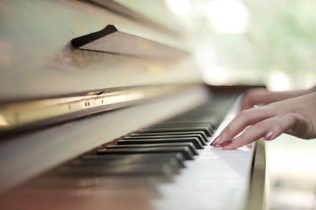 Klaviertastatur mit den weiblichen händen, die auf ihr spielen