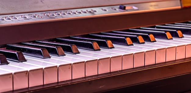 Klaviertasten auf einem schönen farbigen hintergrund schließen.