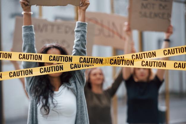 Klebeband, das die augen des mädchens bedeckt. eine gruppe feministischer frauen protestiert im freien für ihre rechte