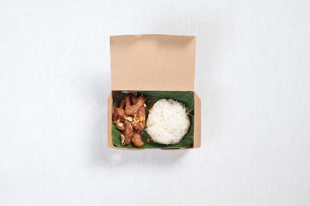 Klebreis mit gebratenem schweinefleisch in eine braune papierschachtel gelegt, auf eine weiße tischdecke gelegt, lebensmittelschachtel, thailändisches essen.