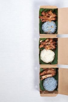 Klebreis mit gegrilltem schweinefleisch und gebratenem schweinefleisch in eine braune papierschachtel gelegt, auf eine weiße tischdecke gelegt, lebensmittelschachtel, thailändisches essen.
