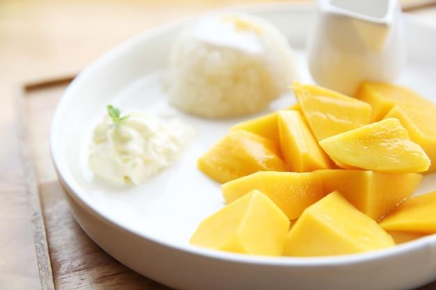 Klebreis mit mango auf holzhintergrund