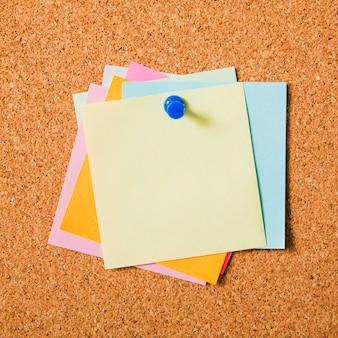 Klebrige postanmerkungen der verschiedenen farben mit druckbolzen auf korkenbrett