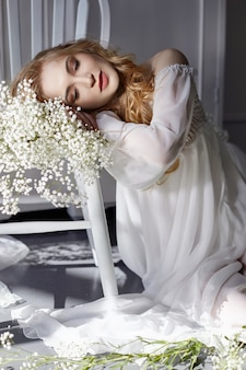 Kleid des weißen lichtes des mädchens und gelocktes haar mit blumen