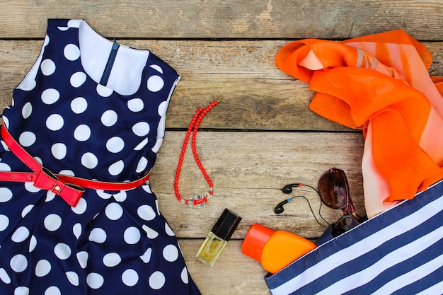 Kleid, handtasche, kopfhörer, parfüm, sonnenbrille, sonnencreme und perlen auf alten hölzernen hintergrund.