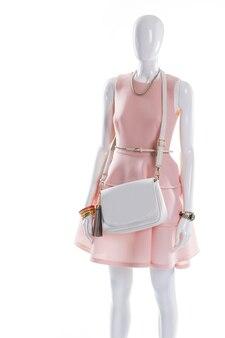 Kleid und geldbörse auf schaufensterpuppe. elegantes outfit auf weiblicher schaufensterpuppe. weißer kleidergürtel und geldbörse. vergoldetes armband und lederhandtasche.