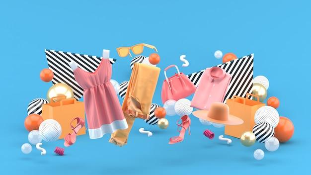 Kleider, hosen, sweatshirts, hüte, geldbörsen, high heels und sonnenbrillen zwischen bunten bällen auf blau. 3d-rendering.