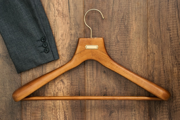 Kleiderbügel mit anzug auf wäschereigeschäft des hölzernen brettes