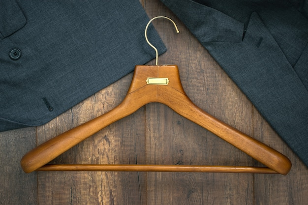 Kleiderbügel mit anzug auf wäschereigeschäftskonzept des hölzernen brettes.