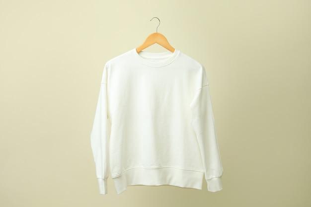 Kleiderbügel mit weißem sweatshirt gegen beige oberfläche