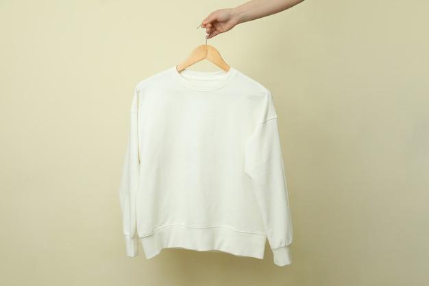 Kleiderbügel mit weißem sweatshirt gegen beige