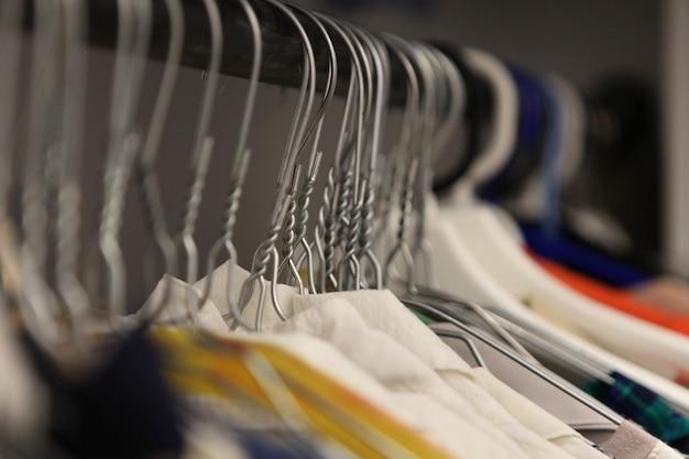 Kleiderbügel nahaufnahme des modegeschäfts. aluminium kleiderbügel mit kleidung. kleidung in einer garderobe. kleidung von damenhemden auf kleiderbügeln im modegeschäft