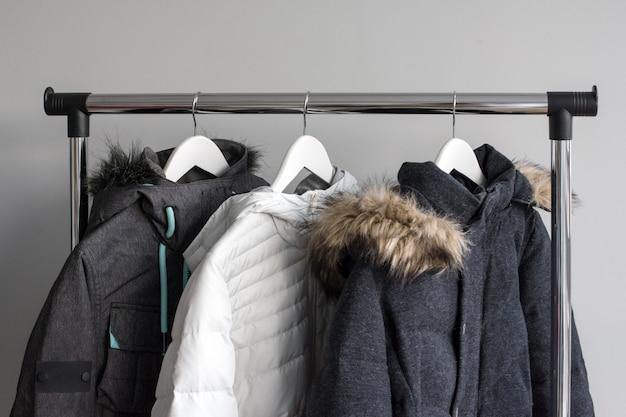 Kleiderbügelständer mit warmen jacken. winterjacken mit pelzkragen hängen an weißen holzbügeln.