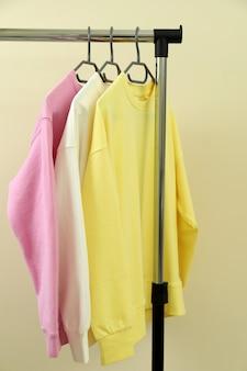 Kleiderschrank mit sweatshirts vor beigem hintergrund
