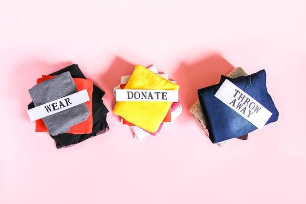 Kleidersortierung in der hausgarderobe zum spenden, tragen und entsorgen mit papiernotizen auf weichem rosa hintergrund.