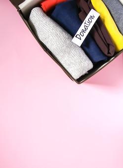 Kleidersortierung in der vertikalen aufbewahrung der garderobe für die spende mit papiernotiz auf weichem rosa hintergrund.
