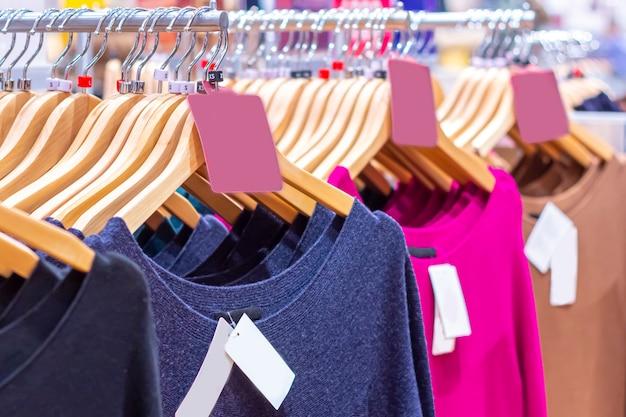 Kleiderständer mit der kleidung der bunten frauen im modernen modespeicher. einkauf und saisonverkauf