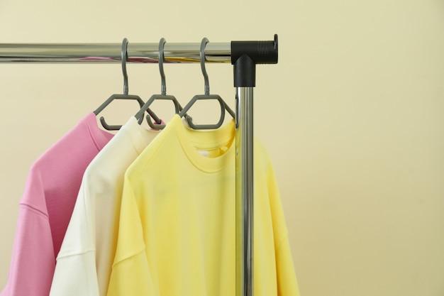 Kleiderständer mit sweatshirts gegen beige oberfläche