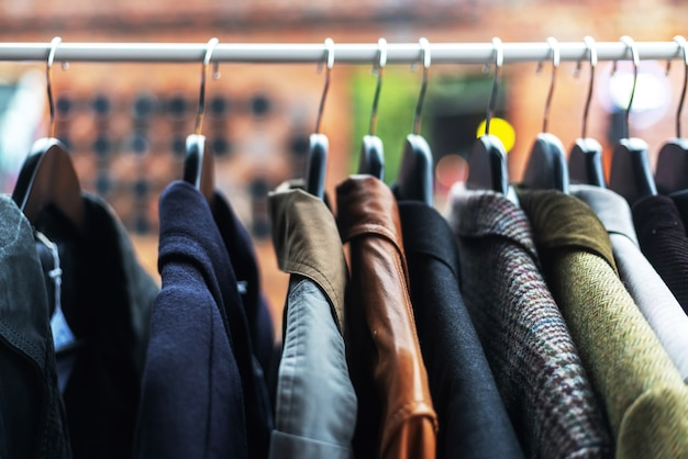 Kleidung auf den kleiderbügeln auf dem flohmarkt, günstiges kleidungskonzept, bild mit weichzeichner