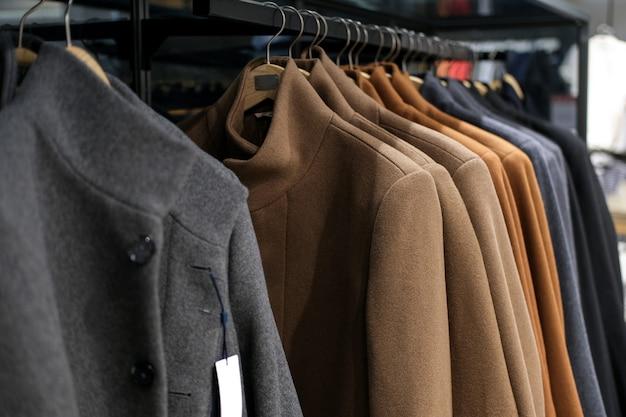 Kleidung auf einem aufhänger herbst- oder wintermantel am bekleidungsgeschäft der männer. saisonzeit der verkäufe und rabatte.